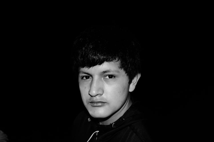 Portrait Of Teenage Boy Against Black Background