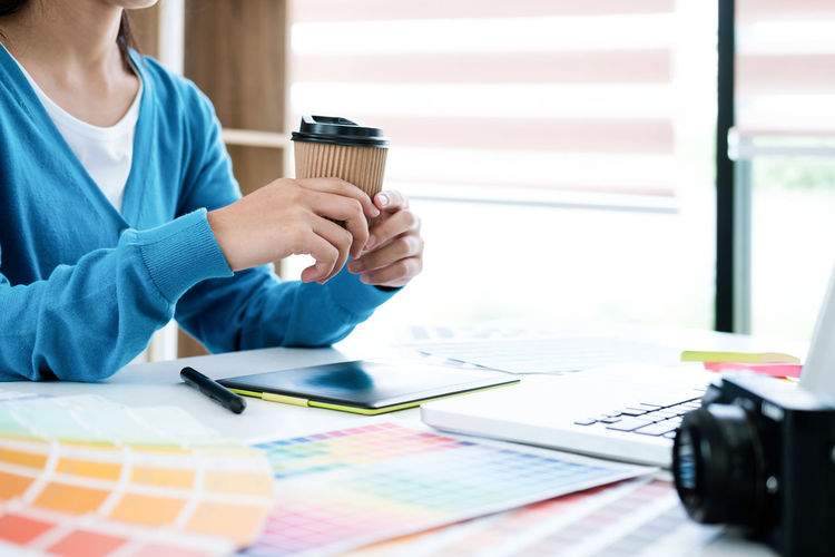 Midsection of businesswoman holding coffee cup while sitting at desk