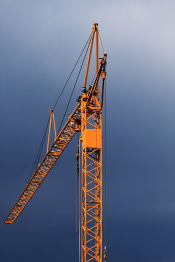 Low Angle View Of Yellow Crane Against Cloudy Sky