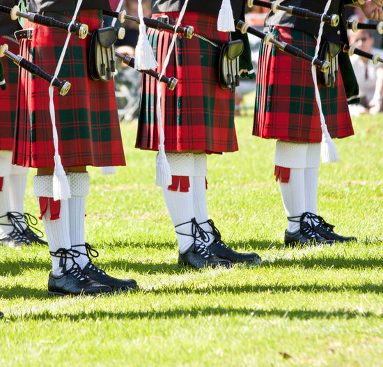 Low Section Of Bagpipers On Green Field