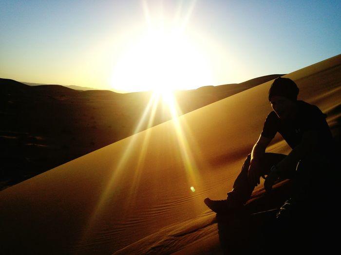 Silhouette man sitting on sand dune against sky at sahara desert during sunny day