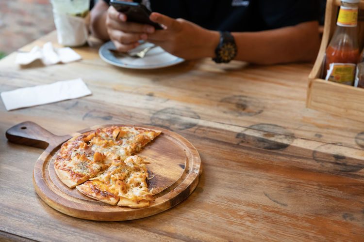 Table Food And Drink Food Real People Freshness One Person Indoors  Wood - Material Lifestyles Leisure Activity Human Hand Midsection High Angle View Ready-to-eat Day Unrecognizable Person Baked Focus On Foreground Hand