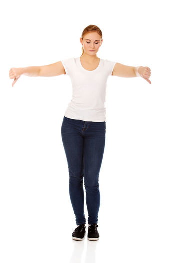 Full length of young woman showing thumbs down sign on white background
