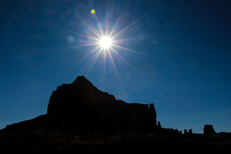 Sky Rock Sun Lens Flare Rock Formation Rock - Object Sunlight Nature Sunbeam Beauty In Nature Solid Tranquility Tranquil Scene Scenics - Nature Low Angle View Non-urban Scene No People Physical Geography Silhouette Land Outdoors Bright Monument Valley Arizona