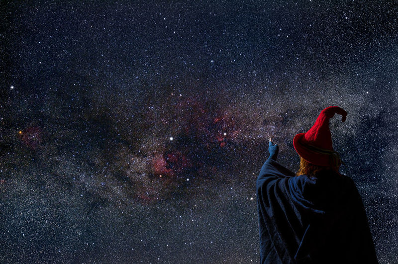 Rear view of man standing against star field at night