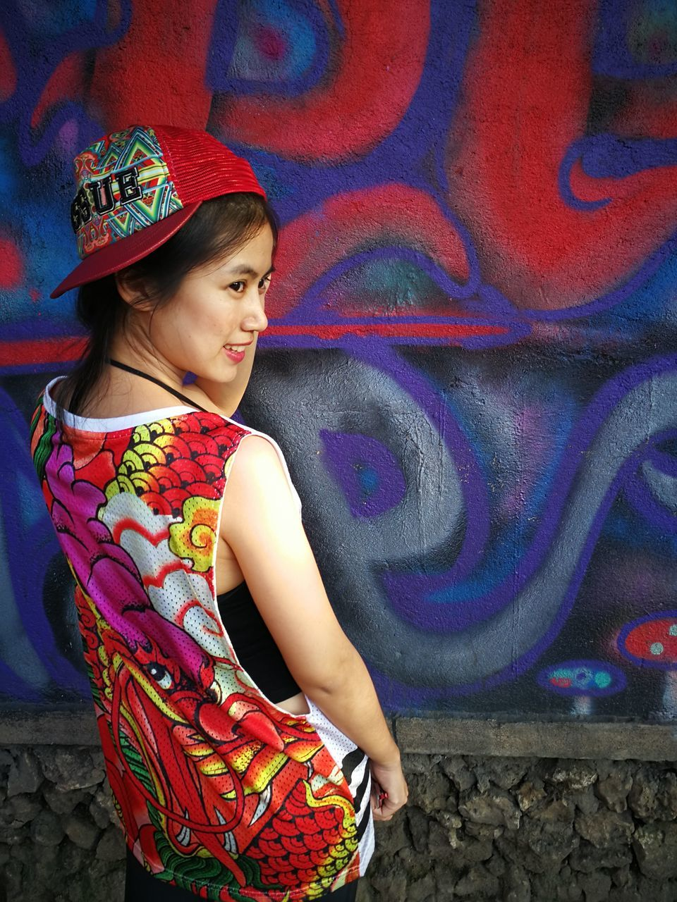 Rear View Of Young Woman Standing Against Graffiti Wall