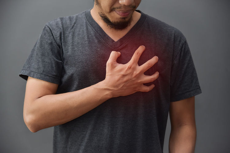 Midsection of man with chest pain against gray background