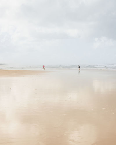 Children playing at beach against cloudy sky