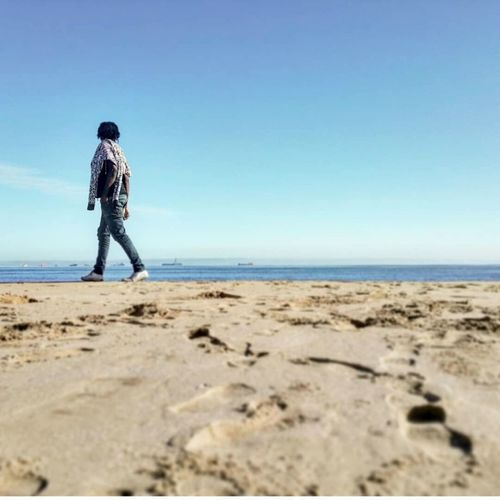 Full length of man walking on shore at beach against blue sky