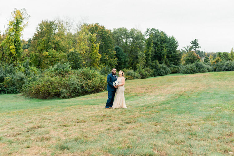 Couple standing on field against trees