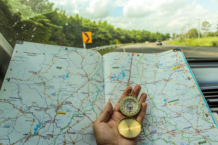 Close-up of person hand holding navigational compass with map by car windshield