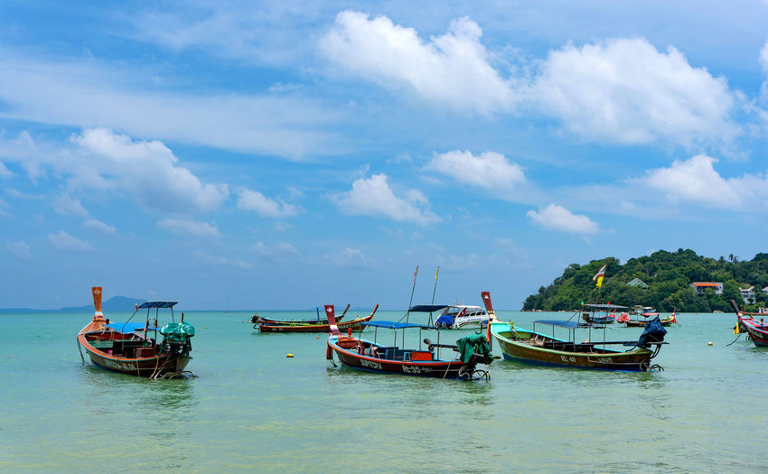 Fishing boats moored in sea against sky