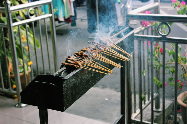 High angle view of satay cooking on barbeque at market stall