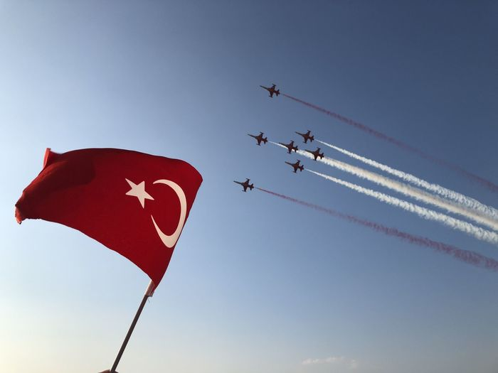 Low angle view fighter plane flying against flag in sky