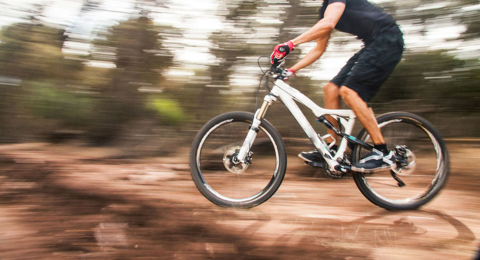 Blurred motion of man riding bicycle on dirt road