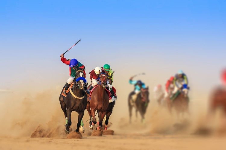 People Riding Horse On Desert Against Sky