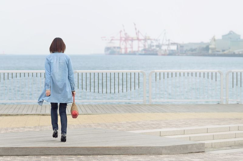 Rear View Of Woman In City By Sea