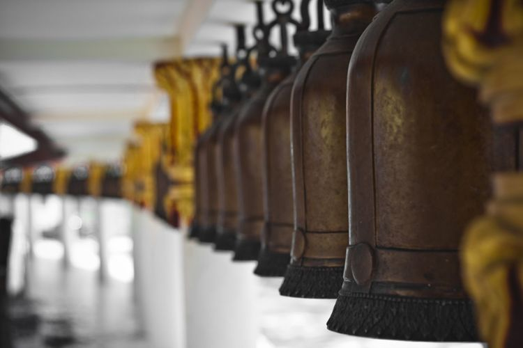Close-up of metallic bells in buddhist temple