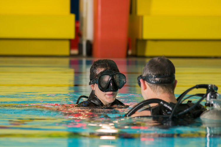 Close-up of man and woman scuba diving in swimming pool