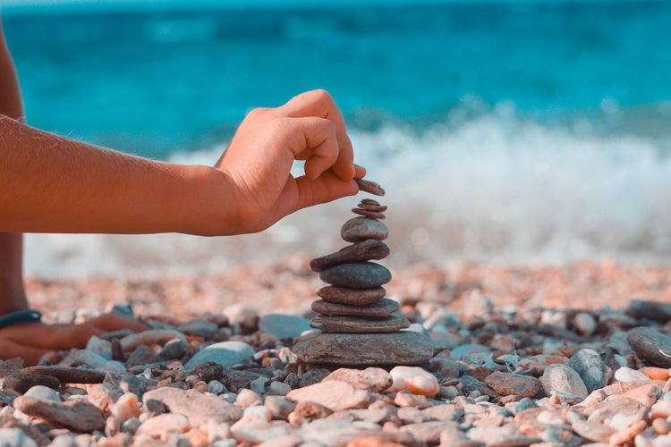 Cropped hand stacking pebbles at beach