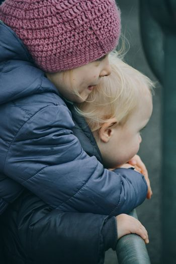Sister and brother embrace outdoors in wintertime
