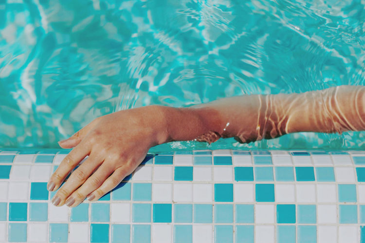 Low section of person lying on swimming pool