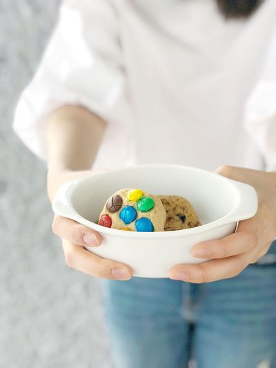 A woman hand hold white ceramic plate with m&m cookie ,white shirt and blue jeans Chocolate Chocolate Chip Decoration Pastry Topping Colorful M&m Chocolate Chip Chocolate Colorful Lifestyles Gift Unhealthy Hand Sugar Food Baked Bakery Cookie Desserts Dessert Sweet Cookie One Person Holding Women Human Body Part Bowl Healthy Lifestyle Standing