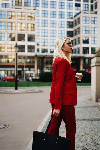 Side view of woman wearing red suit walking on street