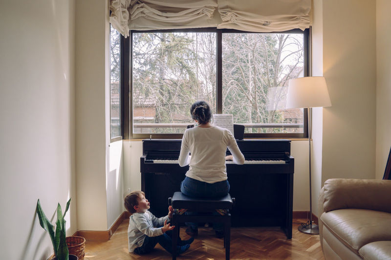 Rear view of mother and son playing piano at window