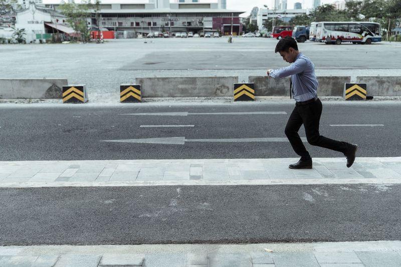 Full length of man crossing road