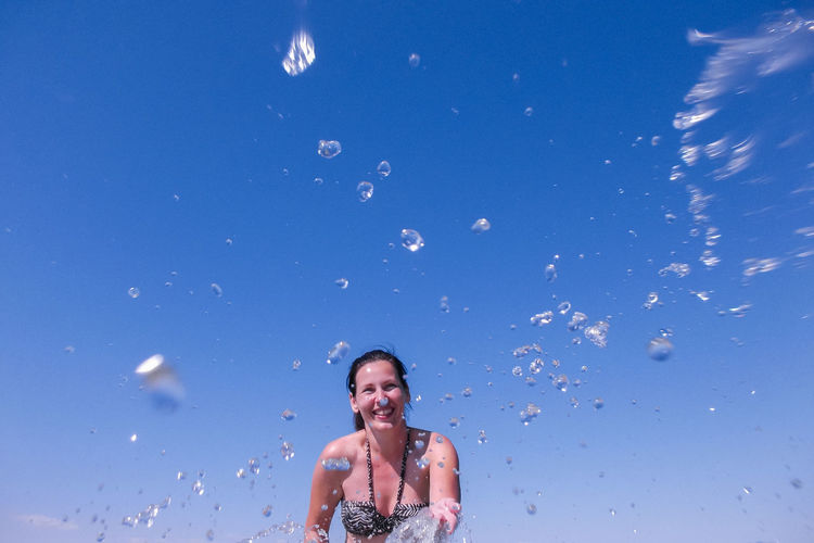 Smiling woman splashing water against clear blue sky during sunny day