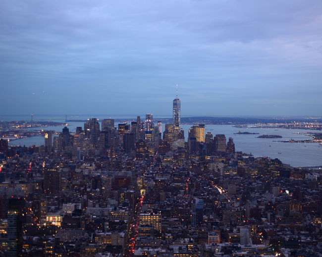High angle view of illuminated buildings against river at manhattan