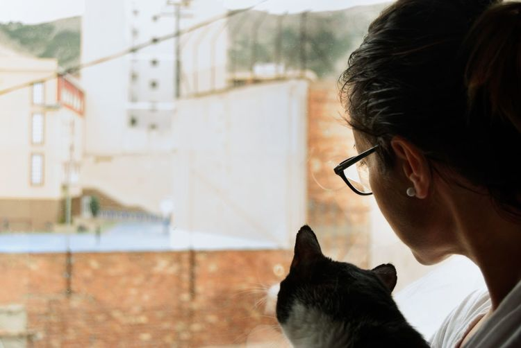 Close-up of woman with cat looking through window at home