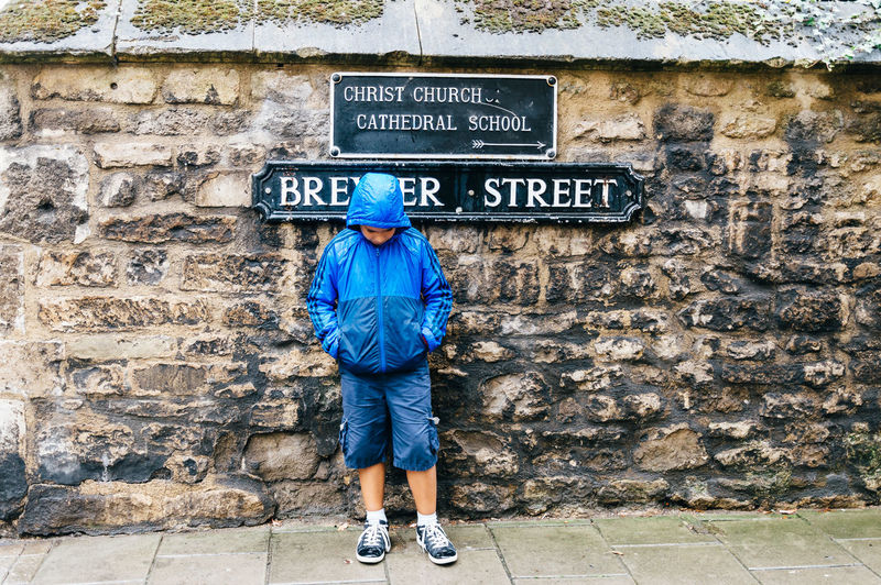 Kid with a blue raincoat against a stone wall with a street name in Oxford Blue Brick Wall Casual Clothing City Day Full Length Information Sign Kid Leisure Activity Lifestyles Outdoors Oxford Raincoat Relaxing Silhouette Stone Art Street Sign Today's Hot Look Town Urban Vintage Wall - Building Feature