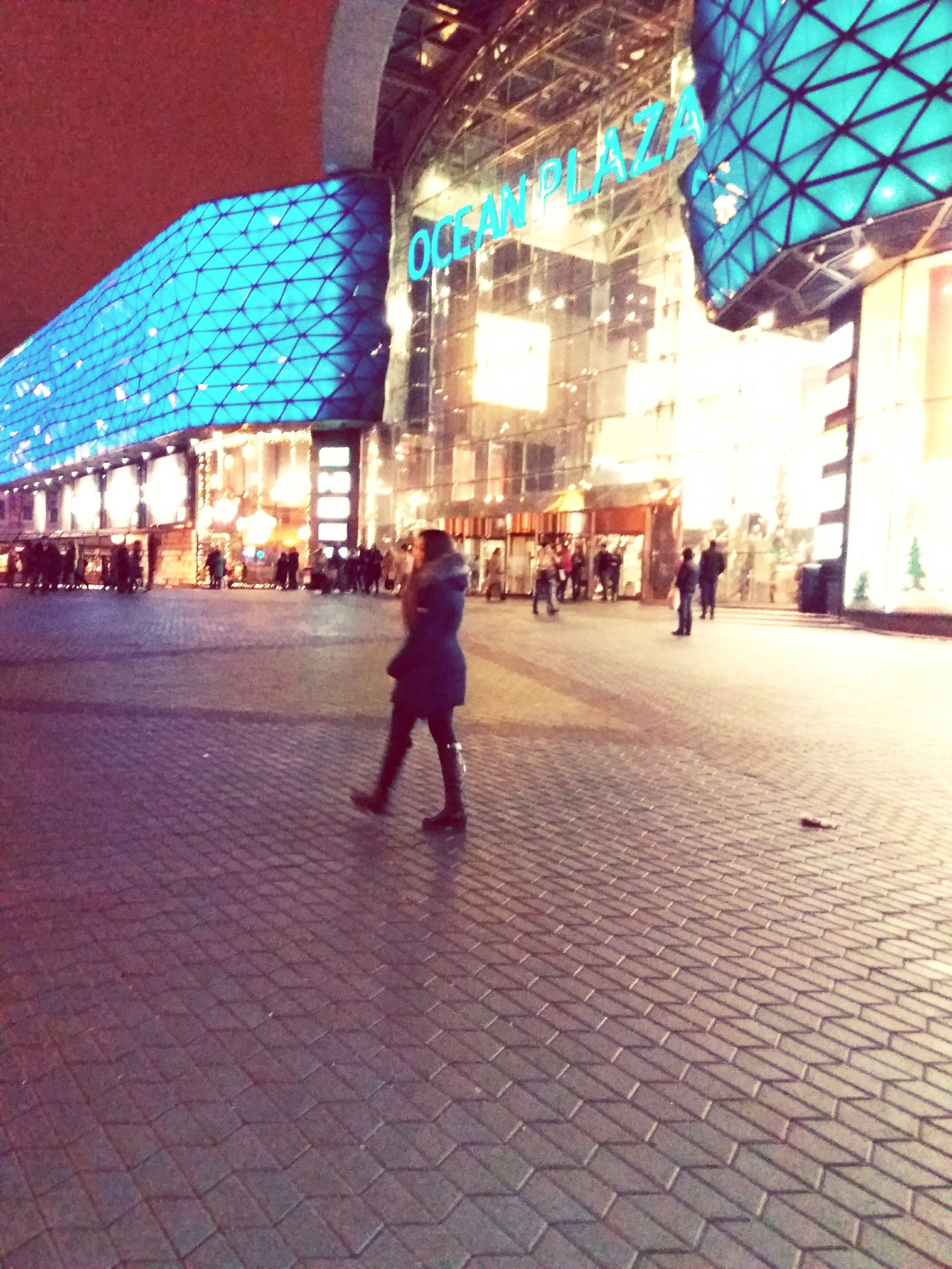 walking, illuminated, built structure, architecture, city, lighting equipment, building exterior, real people, christmas, full length, night, men, outdoors, large group of people, people, adults only, adult, only men, ice rink