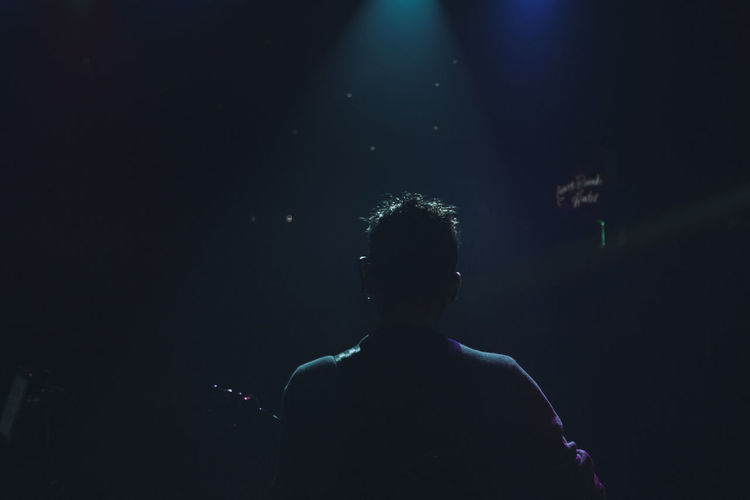 Rear view of silhouette man standing at music concert