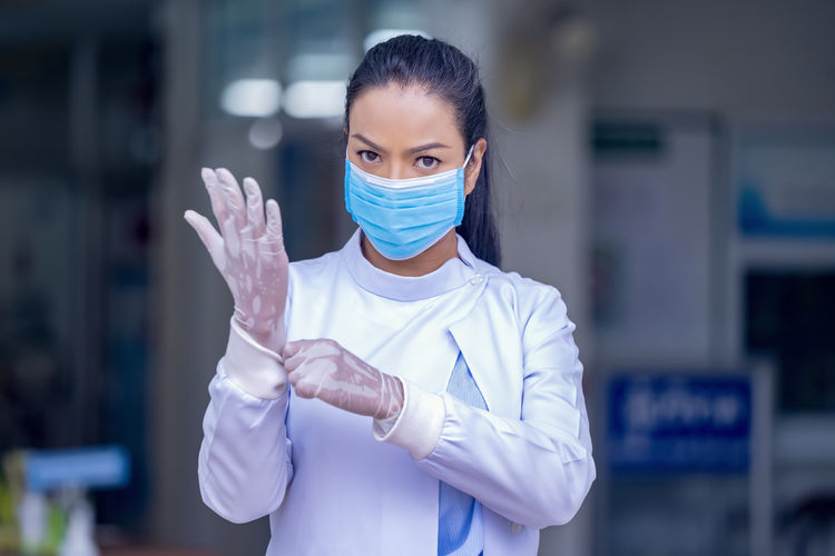 Portrait of female doctor wearing mask and gloves