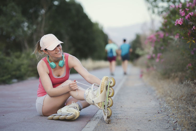 Blond girl wearing a pale pink cap and sports clothes sitting on the woman getting ready for skating in the park with her headphones on listening to the music. Adult Casual Clothing Clothing Day Focus On Foreground Full Length Hairstyle Hat Incidental People Leisure Activity Lifestyles Nature One Person Outdoors Plant Portrait Real People Sitting Sun Hat Women Young Adult
