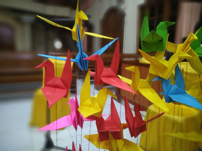 Close-up of multi colored umbrellas hanging on paper
