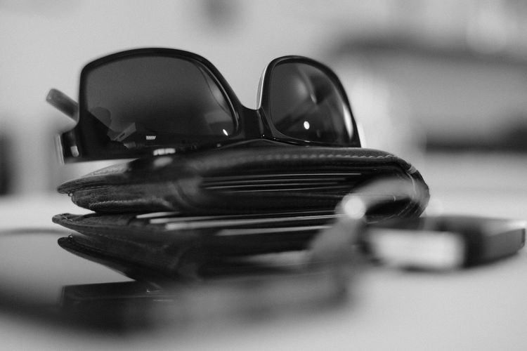 Close-up of sunglass and wallet on table