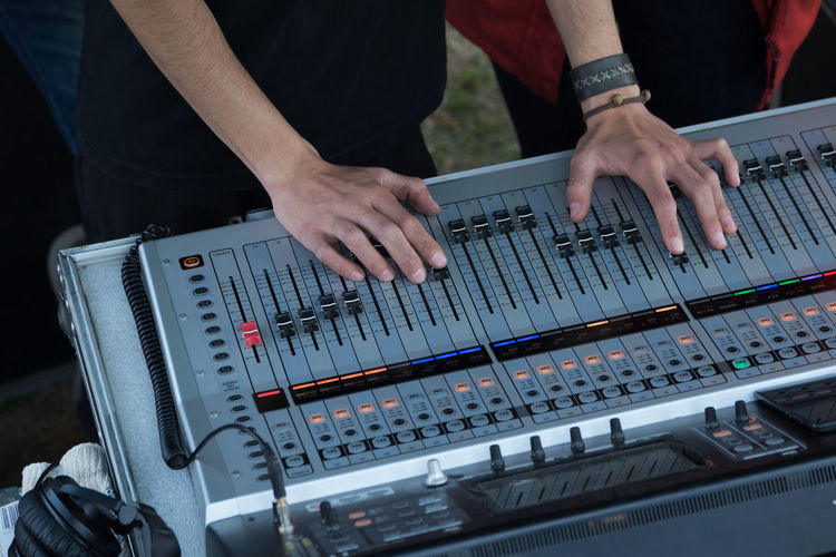 Audio Equipment Adjusting Arts Culture And Entertainment Audio Console Audio Equipment Concert Control Equipment Finger Hand Human Body Part Human Hand Men Midsection Mixing Music Nightlife Occupation Real People Recording Recording Studio Sound Mixer Sound Recording Equipment Studio Technology