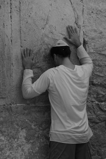 Rear view of man standing by wall