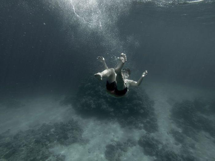 Close-up of man swimming underwater
