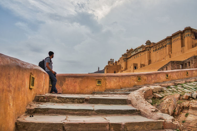 Tourist Standing On Staircase In Fort Against Cloudy Sky