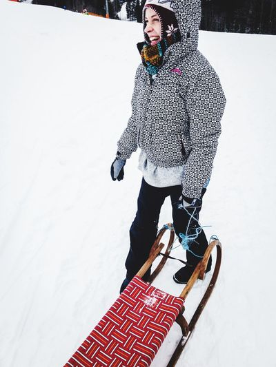 happy young woman with sleigh in the snow Snow Winter One Person Vacations Young Adult Lifestyles Full Length Cold Temperature Warm Clothing Leisure Activity Looking At Camera Standing Portrait Outdoors Sport Ski Holiday Real People Smiling
