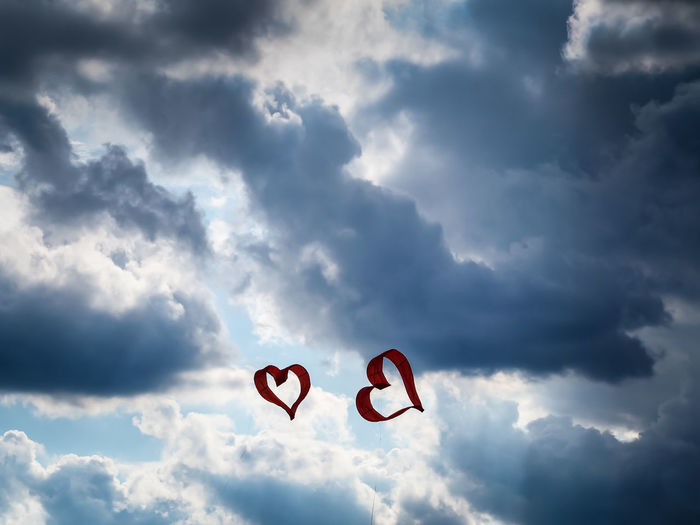 Low angle view of heart shape kites flying against cloudy sky