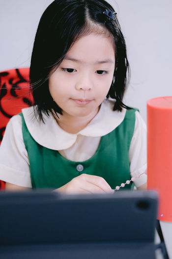 Girl looking away while sitting on mobile phone