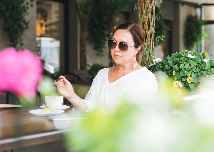 Portrait of woman holding sunglasses at restaurant table