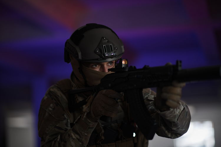 Man holding camera at illuminated nightclub