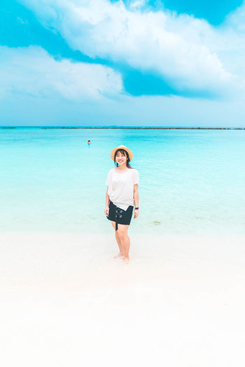 Full Length Of Woman Standing On Shore At Beach Against Sky